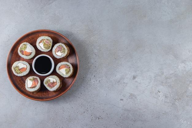 Rolinhos de sushi com molho de soja colocados num prato de madeira.