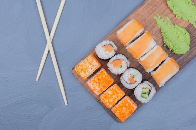 Rolinhos de sushi com molho de wasabi em travessa de madeira