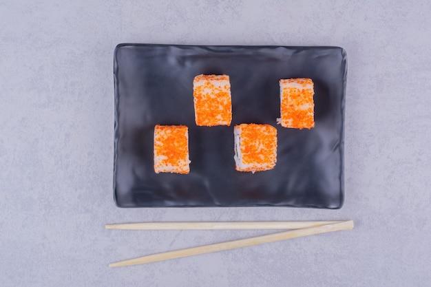 Rolinhos de sushi com salmão em travessas de cerâmica preta