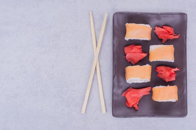 Rolinhos de sushi com salmão em uma travessa de cerâmica preta.