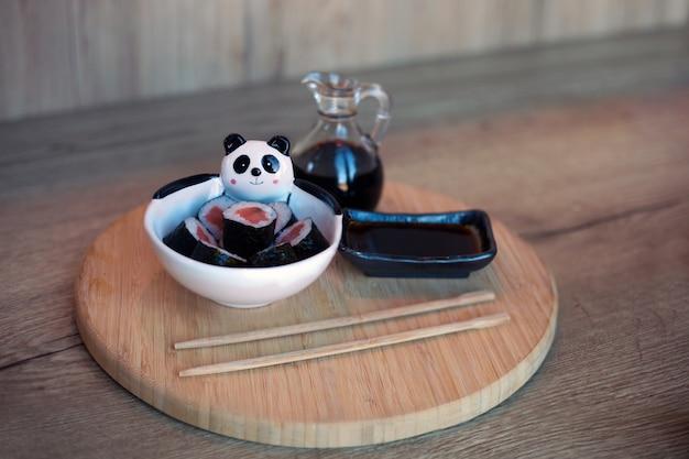 Rolinhos de sushi com salmão feitos para crianças em mesa de madeira com pauzinhos e comida coreana de soja