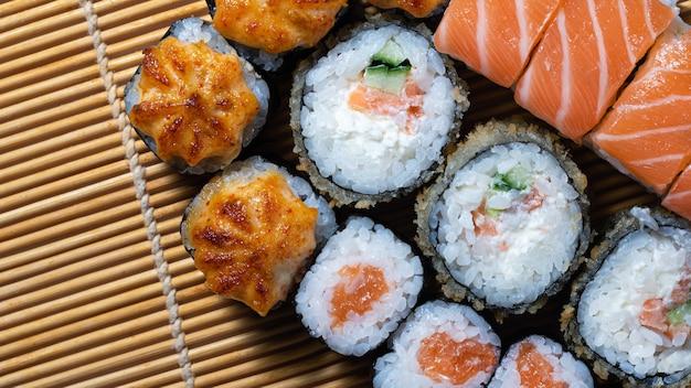 Rolinhos de sushi de culinária japonesa colocados em uma esteira de bambu vista de cima