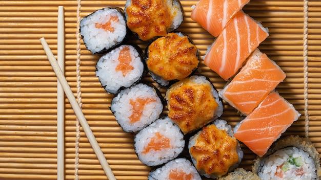 Rolinhos de sushi de culinária japonesa em uma vista superior de esteira