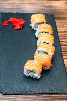 Rolinhos de sushi de peixe com salmão, pauzinhos de wasabi pretos servindo tábua de madeira. restaurante com serviço de alimentação