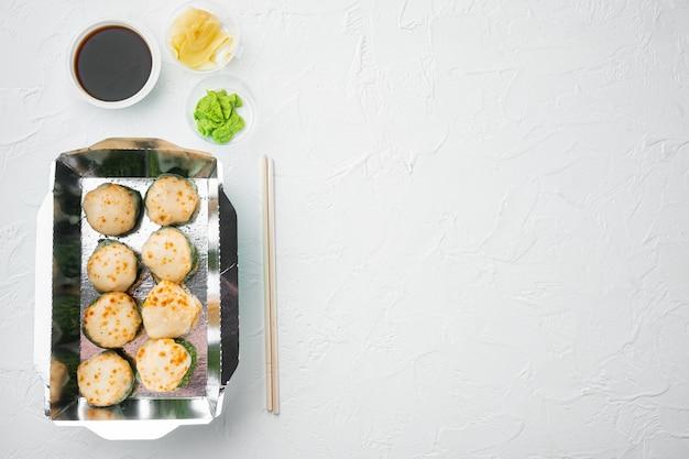 Rolinhos de sushi em recipiente para viagem, em pedra branca