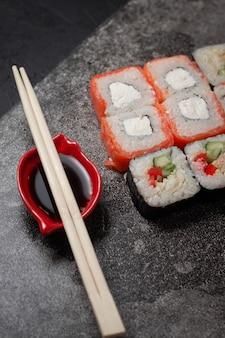 Rolinhos de sushi em um fundo de pedra escura com varas de bambu e molho de soja