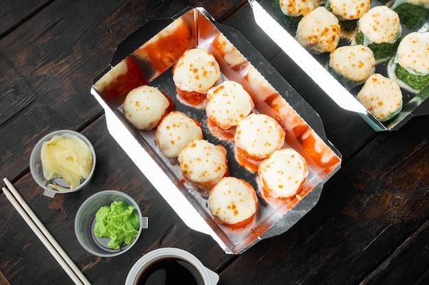 Rolinhos de sushi em um recipiente para viagem, na velha mesa de madeira escura
