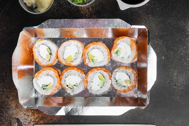 Rolinhos de sushi em vasilha para viagem, em estilo rústico escuro antigo