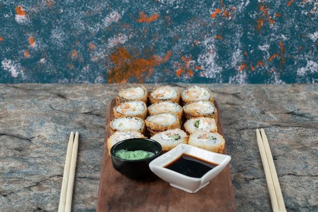 Rolinhos de sushi fritos quentes com molho de soja e wasabi.