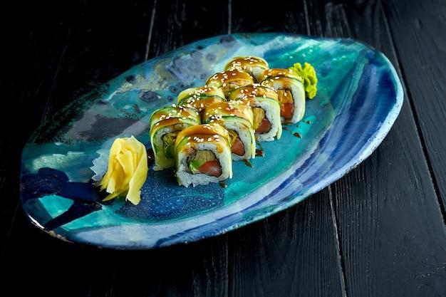 Rolinhos de sushi japonês fresco com pepino, molho unagi e salmão, servidos em um prato azul sobre um fundo escuro.
