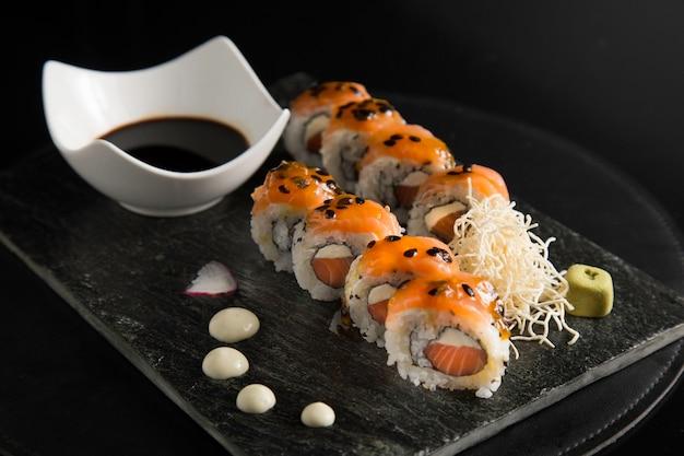 Rolinhos de sushi pasion fruit em um prato com molho de soja