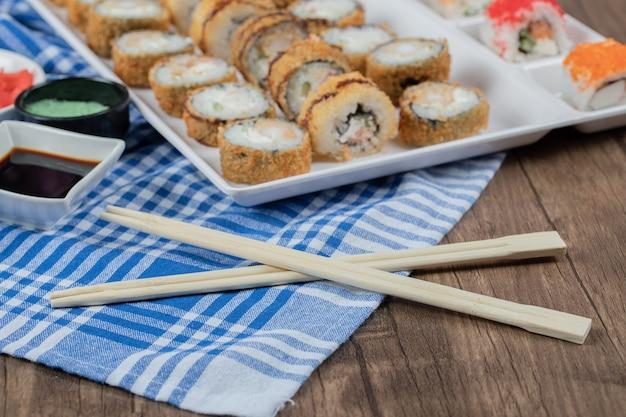 Rolinhos de sushi quentes em uma travessa de madeira com molho de soja, gengibre e wasabi.