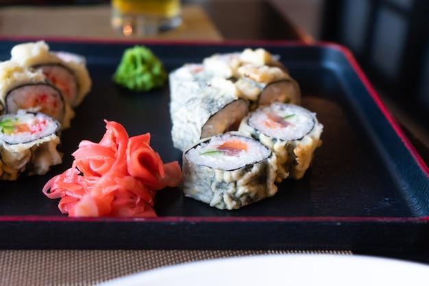Rolinhos, gengibre e wasabi estão na bandeja de servir. comida japonesa no restaurante.