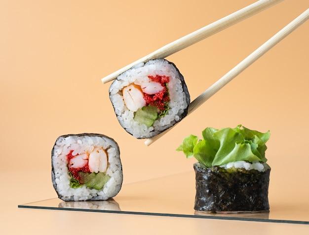Rolinhos japoneses em um prato sendo apanhados com pauzinhos em um fundo laranja claro