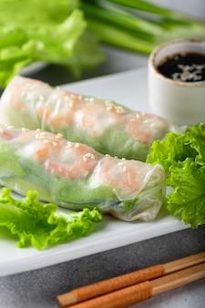 Rolinhos primavera com camarão cenoura pepino cebolinha e macarrão de arroz com foco seletivo