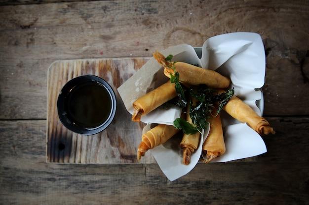 Rolinhos primavera com camarão com molho de pimenta doce. comida asiática em fundo de madeira Foto Premium