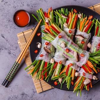Rolinhos primavera com legumes e cogumelos shiitake em um prato.