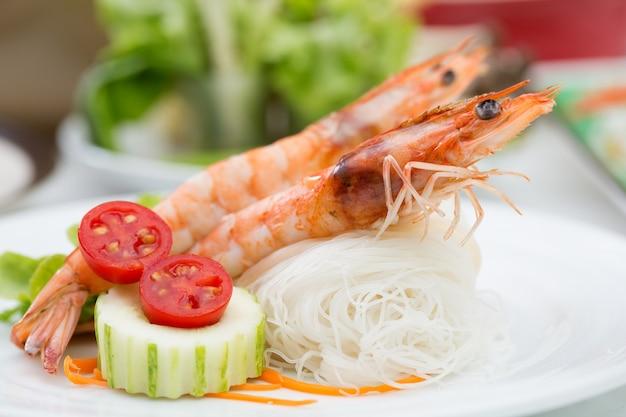 Rolinhos primavera de camarão em um prato branco com aletria.