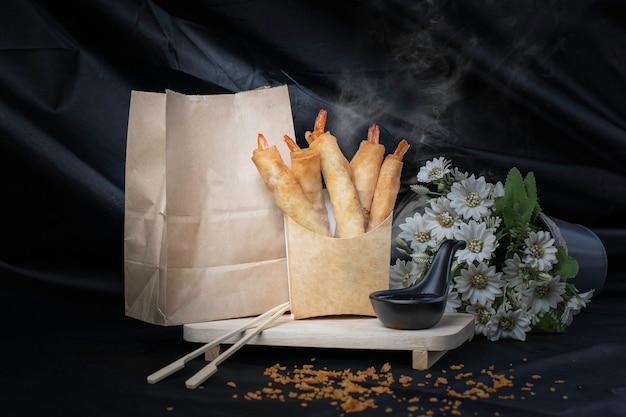 Rolinhos primavera de camarão frito são embrulhados em papel pardo. fundo preto com fumaça de calor