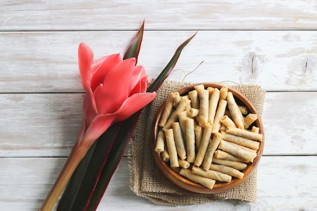 Rolinhos primavera de pato frito fino na mesa de madeira com flores