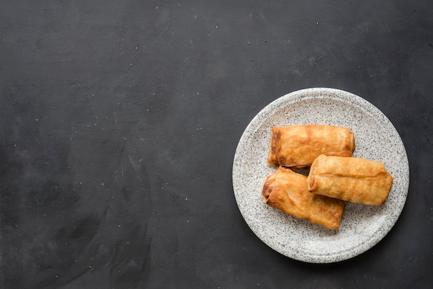 Rolinhos primavera de vegetais fritos com ingredientes frescos servidos e molho azedo em um restaurante oriental