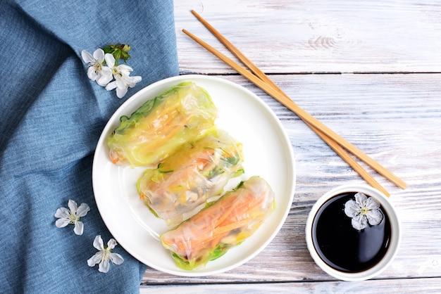 Rolinhos primavera em um prato branco com tecidos e molho de soja