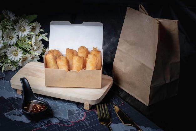 Rolinhos primavera fritos e molho em uma caixa de papel pardo