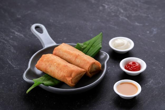 Rolinhos primavera fritos, populares como lumpia ou popia. servido em prato cinzento, mesa de mármore preto. copiar espaço para texto