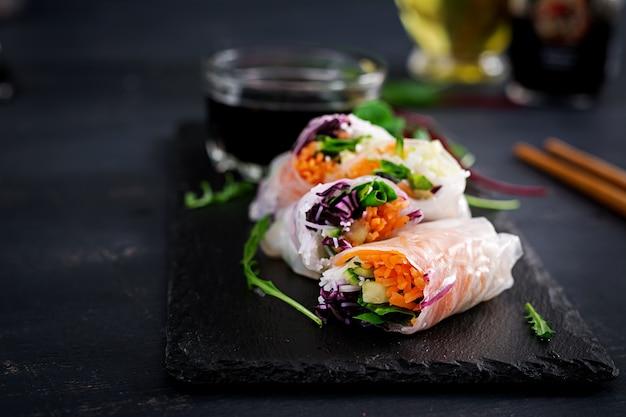 Rolinhos primavera vietnamita vegetariano com molho picante, cenoura, pepino, repolho roxo e macarrão de arroz.