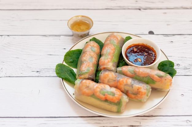 Rolinhos primavera vietnamitas com frango tenro camarão tigre macarrão de arroz manga suculenta ervas frescas em uma tábua de madeira molho de gergelim