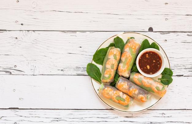 Rolinhos primavera vietnamitas com frango tigre camarão ervas frescas em uma placa de madeira