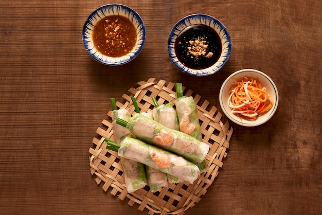 Rolinhos primavera vietnamitas - papel de arroz, alface, salada, aletria, macarrão, camarão, molho de peixe, pimentão doce, soja, limão, veletables. copie o espaço. comida asiática e vietnamita. cozinha tradicional nacional
