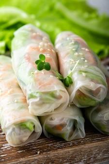 Rolinhos primavera vietnamitas tradicionais com camarão, cenoura, pepino, cebolinha e macarrão de arroz, foco seletivo