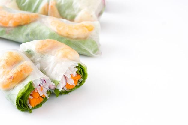 Rolinhos vietnamitas com legumes, macarrão de arroz e camarão com molho de pimentão doce isolado no branco