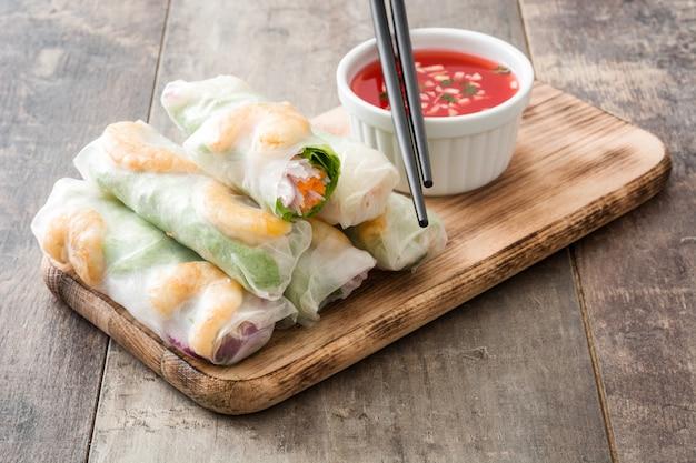 Rolinhos vietnamitas com legumes, macarrão de arroz e camarão com molho de pimentão doce na superfície de madeira