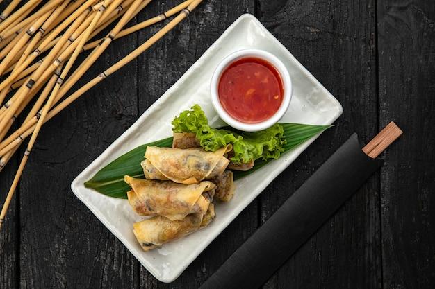 Rolinhos vietnamitas com vegetais, macarrão de arroz e camarões com molho de pimenta doce em superfície de madeira