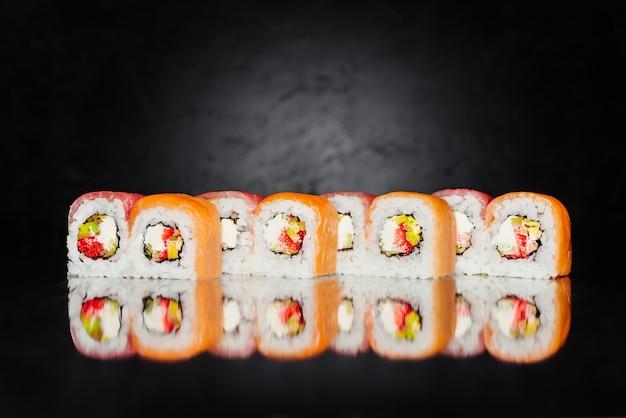 Roll filadélfia feita de salmão, atum, pepino, nori, arroz em conserva
