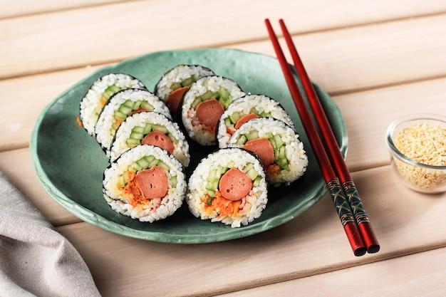 Roll gimbap coreano (kimbob) com salsicha, cenoura, omelete, carne de caranguejo e arroz. envolva com lavador de algas. servido em prato tosca com pauzinho