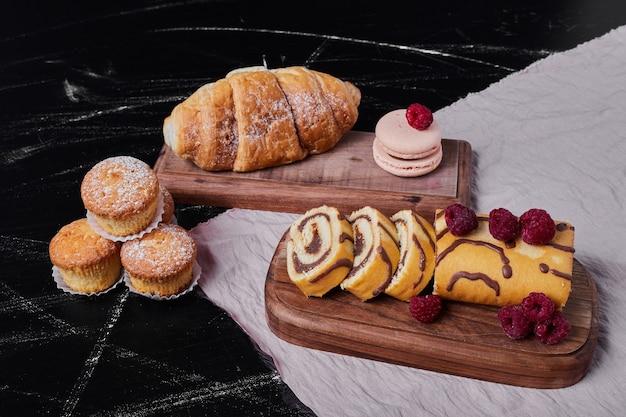 Rollcake com frutas em uma travessa com muffins.