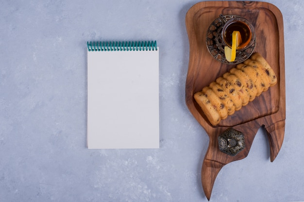 Rollcake servido com chá earl grey em uma travessa de madeira com um caderno de lado