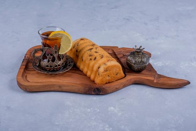 Rollcake servido com chá earl grey em uma travessa de madeira no espaço azul