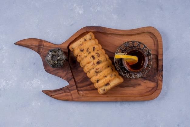 Rollcake servido com chá earl grey em uma travessa de madeira, vista de cima