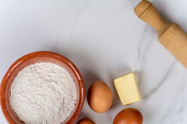 Rolling pin, ovos, farinha e manteiga.