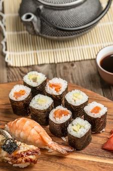 Rolls com abacate e atum, sushi variado na placa de madeira