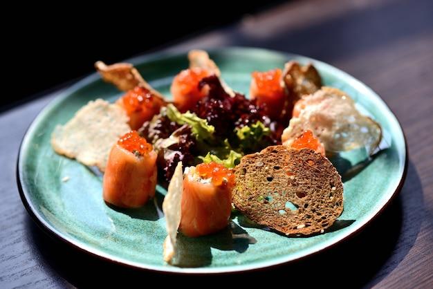Rolls com salmão, queijo, caviar vermelho e bolachas