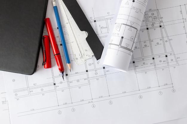 Rolls de plantas da arquitetura e planos da casa nas ferramentas de desenho da tabela e do arquiteto.