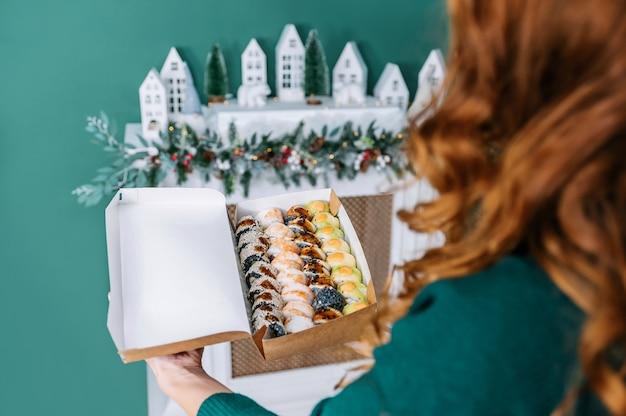 Rolls em uma caixa de artesanato na mão da menina no contexto do interior de uma casa.