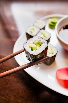 Rolls in nori algas com abacate, gengibre em conserva e molho de soja. culinária asiática, prato tradicional - sushi.
