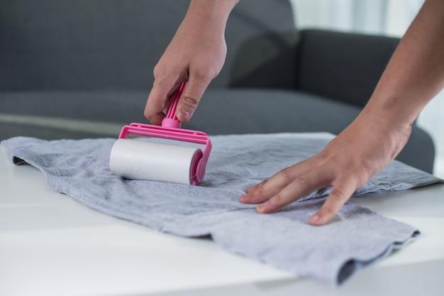 Rolo adesivo para pano de limpeza em uma camiseta. lint roller with pink handle.