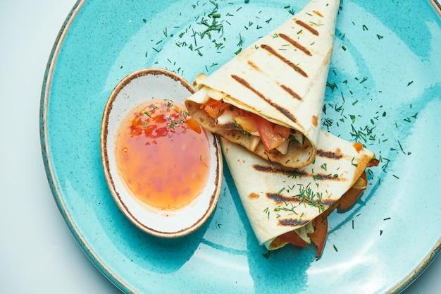 Rolo apetitoso de shawarma com carne, salada e molho caseiro em pão pita fino em chapa azul isolada na superfície cinza. cozinha oriental. quibe fatiado com carne grelhada.